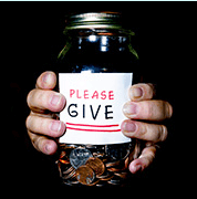 """Hands holding jar with a """"please give"""" sign on it"""