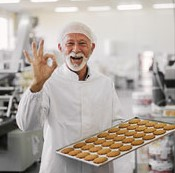 Old man baker holding pan with cookies